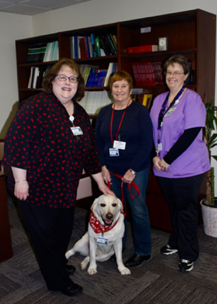 Pictured from left, Donna M. Laudati, Office Manager and Assistant to the Chair of Obstetrics and Gynecology, Murie Nussbaum, Pet Therapy Volunteer, and her dog Will, and Jacqueline Canete, Pet Therapy Coordinator